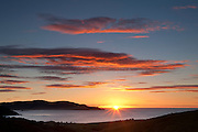 The sun rises over the Catlins Heads near Owaka in southeastern New Zealand.