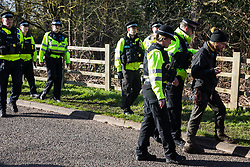 Denham, UK. 6 February, 2020. Police officers move on an environmental activist from Extinction Rebellion who was walking at a snail's pace along a road in order to block a security vehicle and truck delivering fencing and other supplies to be used for works associated with the HS2 high-speed rail link close to the river Colne at Denham Ford. Works planned in the immediate vicinity include the felling of trees and the construction of a Bailey bridge, compounds and fencing, some of which in a wetland nature reserve forming part of a Site of Metropolitan Importance for Nature Conservation (SMI).