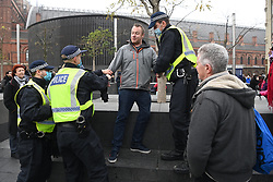 © Licensed to London News Pictures. 28/11/2020. London, UK. A protester is arrested by police officers for taking part in the Unite For Freedom Anti Covid-19 lockdown demonstration in Kings Cross, London. Organised by the group Stand Up X, the protesters are against the current lockdown regulations and anti-vaccination for the Covid-19 disease. Photo credit: London News Pictures