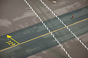 Aerial view (from control tower) of airport ramp marshal at London Heathrow airport.