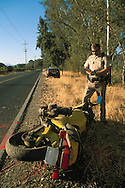 CHP Highway Patrol police officer writing up an accident report after a motorcyle crash on two lane rural country road in Napa Valley, California CHP officer investigating road accident, near St. Helena, Napa Valley, Napa County, CALIFORNIA