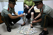 SHENZHEN, CHINA - JUNE 07: (CHINA OUT) <br /> <br /> Armed police officers pick off US dollars tied on a woman\'s legs on June 7, 2016 in Shenzhen, Guangdong Province of China. Armed police of Guangdong Frontier Defense Bureau arrested a woman tying 220,000 US dollars on her legs and a woman hiding over 3,000 memory cards at her private part when they were checked at the entry to Shenzhen on Tuesday<br /> ©Exclusivepix Media