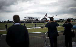 © London News Pictures. 09/07/2012. Farnborough, UK. Businessman and women watch a Qatar Arlines Dreamliner Bowing 787 giving a flight demonstration on day one of the Farnborough International Airshow, in Farnborough, Hampshire, UK on July 9, 2012. FIA is a seven-day international trade fair for the aerospace industry which is held every two years at Farnborough Airport . Photo credit: Ben Cawthra/LNP.