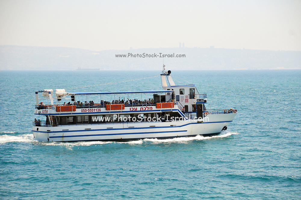 Tourist boat out of the Old Port of Acre, Israel. Mount Carmel and Haifa in the distant background