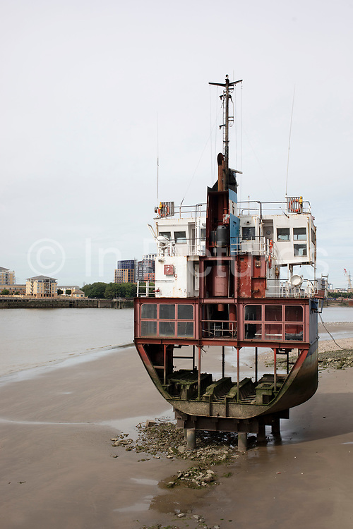 A Slice of Reality, artwork sculpture by Richard Wilson standing on the riverbank of the River Thames in London, United Kingdom. The work comprises of a sliced vertical section of an ocean going sand dredger. The slicing of the vessel opened the structure, leaving it exposed to the effects of weather and tide.