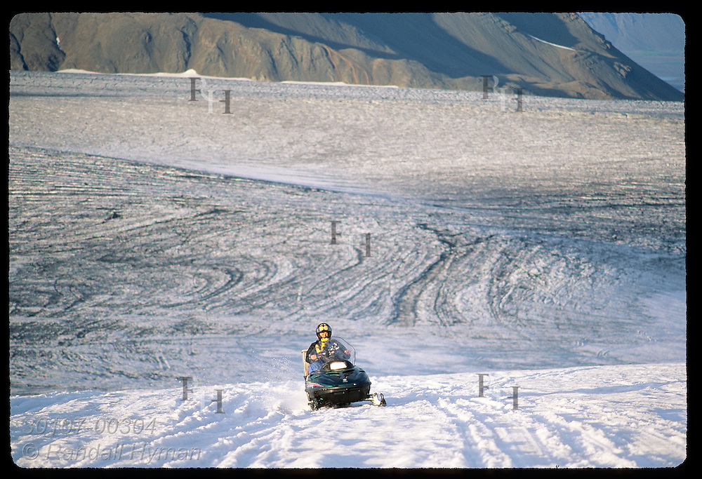Glacier Tours guide races up Vatnajokull glacier on a snowmobile in late afternoon in September; southeast Iceland.