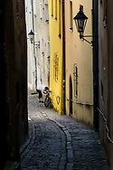 Man locking up a bicycle in an alley, Passau Germany