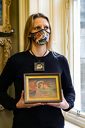 Bonhams picture specialist May Matthews wears 'Morning', an enamelled metal plaque, inscribed and dated 'Morning/1914' by Phoebe Anna Traquair HRSA (1862-1936).  The plaque is mirrored in the mask May is wearing.<br />