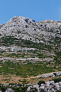 Hilltop with typical undulating rock formation. Chalk rock with dry underbrush. Mount Sveti Ilija mountain. Orebic town. Peljesac peninsula. Dalmatian Coast, Croatia, Europe.