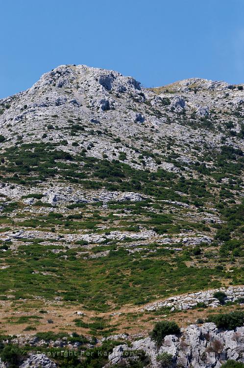 Hilltop with typical undulating rock formation. Chalk rock with dry underbrush. Mount Sveti Ilija mountain. Orebic town. Peljesac peninsula. Dalmatian Coast, Croatia, Europe.