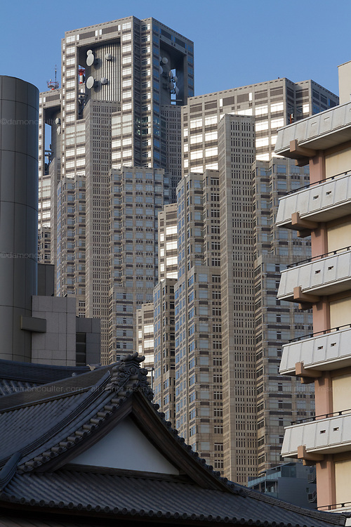Tokyo Metropolitan Government Towers behind apartment buildings and a shrine roof in Shinjuku, Tokyo, Japan. Thursday February 15th 2018