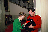"""Washington, DC. 1984/12/10  First Lady Nancy Reagan during a taping of a """"Christmas in the White House"""" special. She is playing with the Reagan's new puppy """"Lucky""""  Sitting next to her is one of the White House electrician who is actually the person who watches after all of the presidential pets.<br /> <br /> Photograph by Dennis Brack"""