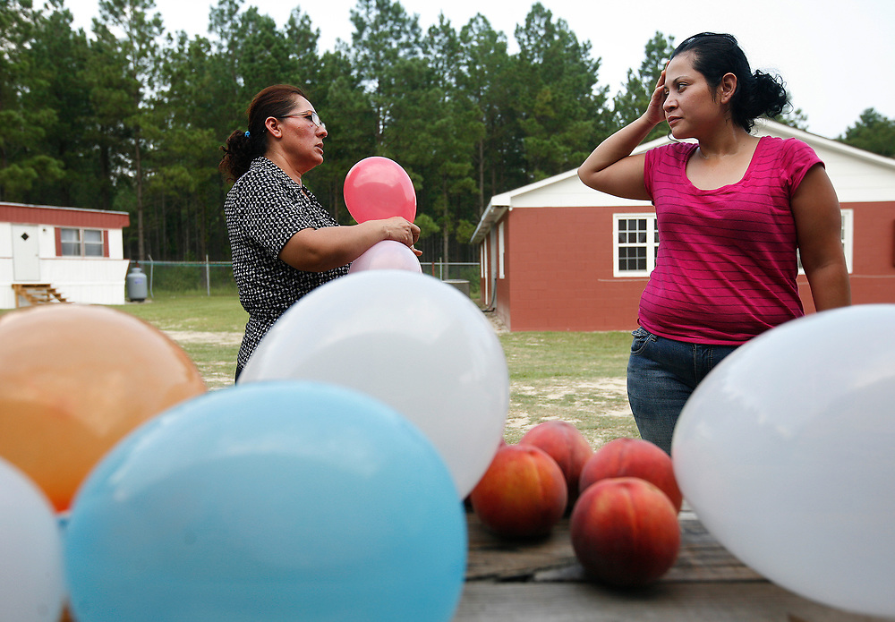 Maria Elena and LiLiana Manrique Zavala prepare decorations for a co-workers birthday party celebration at the compound where they live with other migrant workers.