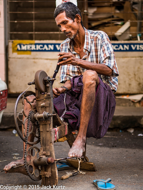 """06 NOVEMBER 2015 - YANGON, MYANMAR: A knife grinder with his pedal powered grinding stone works on a Yangon street. He walks through the city announcing his services and sharpens people's knives for the equivalent of few cents each. Some economists think Myanmar's informal economy is larger than the formal economy. Many people are self employed in cash only businesses like street food, occasional labor and day work, selling betel, or working out of portable street stalls, doing things like luggage repair. Despite reforms in Myanmar and the expansion of the economy, most people live on the informal economy. During a press conference this week, Burmese opposition leader Aung San Suu Kyi said, """"a great majority of our people remain as poor as ever.""""  PHOTO BY JACK KURTZ"""