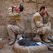 Apr 15, 2010 - Panjwaii, Kandahar, Afghanistan -  (Left to Right) Pvt. John Howard eats breakfeast while an exhasuted Cpl. Adam Hilton mans the radio before patroling in the village of Kairo Kala in Panjwaii (aka Panjway) District west of Kandahar City during a patrol searching for deadly Improvised Explosive Devices (IED's) planted by Taliban insurgents. This area is one of the most volatile and IED riddled areas in the country..(Credit Image: © Louie Palu/ZUMA Press)