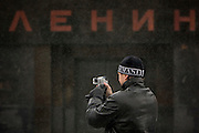 Moscow, Russia, 20/02/2005..A Russian tourist in fake Armani wollen hat uses a digital camera in front of Lenin's tomb on Red Square.