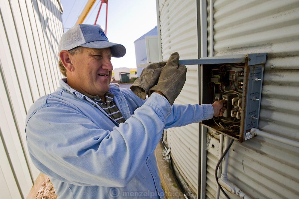 Illinois farmer Gordon Stine checks a mechanical circuit breaker on a drier fan in a silo at his leased farm in St. Elmo, Illinois. MODEL RELEASED.  (Gordon Stine is featured in the book What I Eat; Around the World in 80 Diets.)
