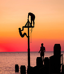 © Licensed to London News Pictures. 03/07/2018. Aberystwyth, UK. A day of unbroken blue skies and searing  heat comes to a beautiful end with people on the seaside pier watching a glorious sunset over Cardigan Bay off Aberystwyth on the west coast of Wales<br /> Photo credit: Keith Morris/LNP