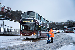 Edinburgh, Scotland, UK. 10 Feb 2021. Big freeze continues in the UK with heavy overnight and morning snow bringing traffic to a standstill on many roads in the city centre. Pic; Bus is freed from snow and slowly drives up The Mound.   Iain Masterton/Alamy Live news