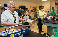 Mr. Donovan hands out D.A.R.E. booklets to his fifth grade students before their ice cream party at Gilford Middle School on Thursday morning.  (Karen Bobotas/for the Laconia Daily Sun)
