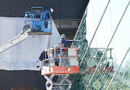 New Paltz, New York - Men on a lift secure glass panels on the addition to the Student Union Building at the SUNY New Paltz while another worker in the background attaches plastic to cover an opening in the old part of the building.