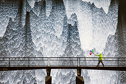 © Licensed to London News Pictures. 17/02/2020. Shap UK. A walker battles with his umbrella in the wind as water cascades down the dam wall of Wet Sleddale reservoir near Shap in Cumbria this morning after days of heavy rain from Storm Dennis. Photo credit: Andrew McCaren/LNP