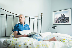 Mature man sitting with newspaper in bed, smiling