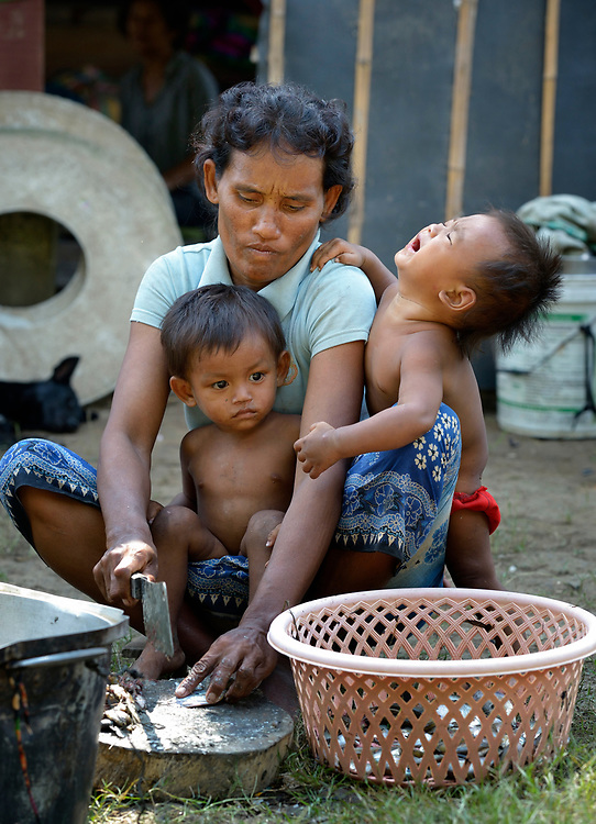 Boung Yong and her ten children live in the village of Phar Thruey in northern Cambodia. Her husband died while working near the Thai border, and Church World Service has provided her with fishing equipment. Here she prepares food while two of her children cling to her.