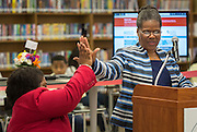 Renita Perry, left, high-fives with Janice Newsum, right, during a library dedication at Attucks Middle School, January 18, 2017.