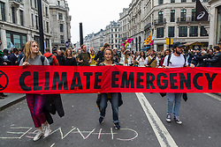 A procession of drummers arrives at Oxford Circus after making their way up Regents Street from Piccadilly Circus, as hundreds of environmental protesters from Extinction Rebellion occupy Oxford Circus, a pink yacht being the focal point of their presence, with traffic denied access to two of London's busiest streets. London, April 16 2019.