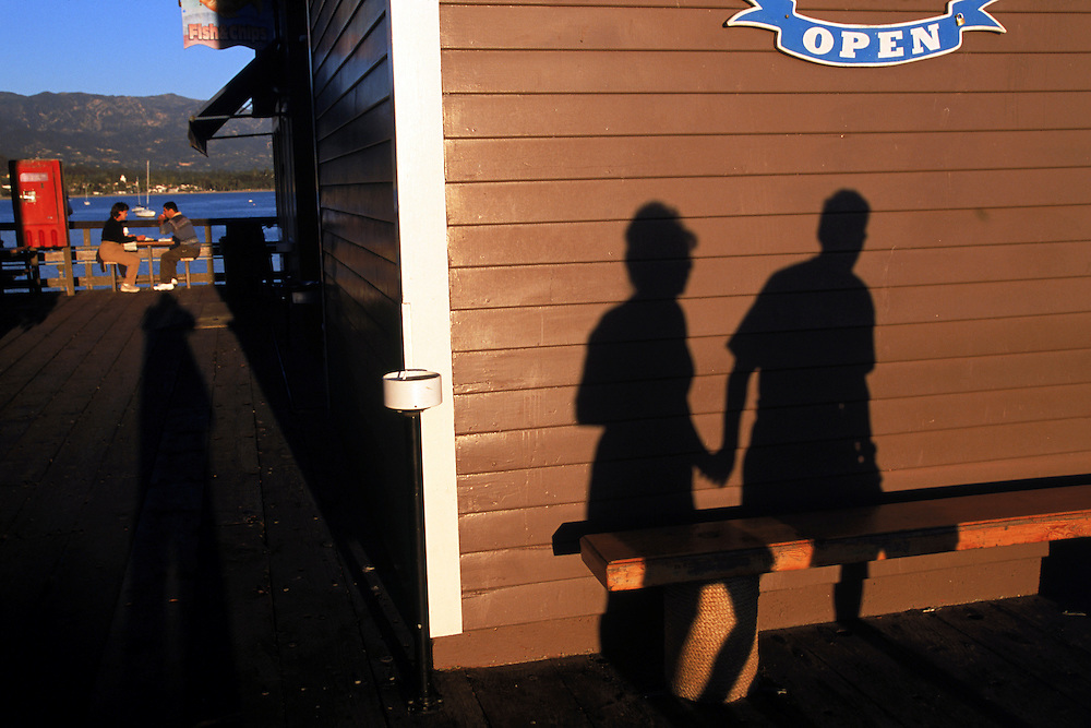 A couple makes their way on the the wharf in Santa Barbara, California in the late afternoon.
