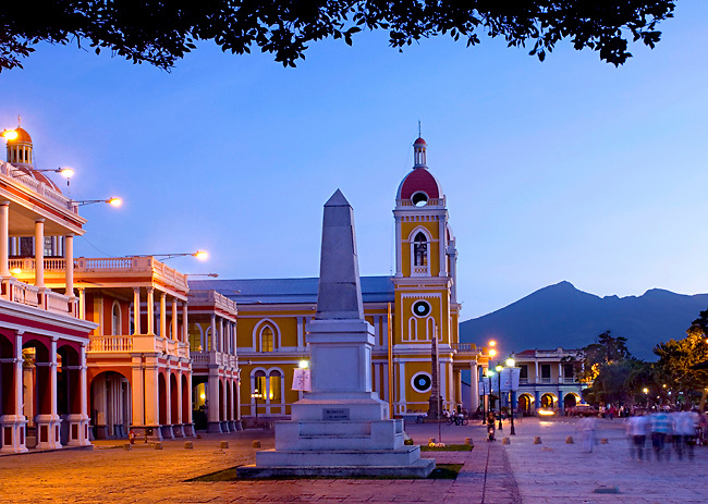 The neoclassical Cathedral of Granada rises above the Spanish colonial homes on Independence Plaza in Granada, Nicaragua.  The Mombacho Volcano can be seen<br /> silhouetted in the background.