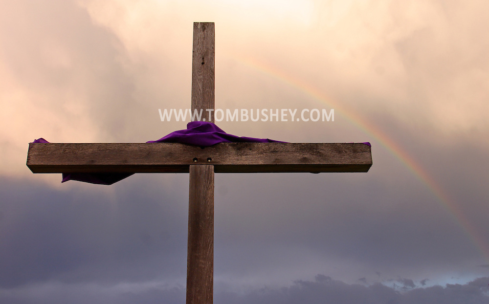 Middletown, N.Y. - A rainbow is visible in the sky behind a cross in front of the North Congregational Church on the Thursday of Holy Week. April 13, 2006.