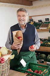 Portrait of a senior shopkeeper selling apples in  the store, Bavaria, Germany
