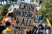 A climate activist from Extinction Rebellion holds a sign calling for green housing for all during a march to a Back The Bill rally in Parliament Square from Buckingham Palace on 1st September 2020 in London, United Kingdom. Extinction Rebellion activists are attending a series of September Rebellion protests around the UK to call on politicians to back the Climate and Ecological Emergency Bill (CEE Bill) which requires, among other measures, a serious plan to deal with the UK's share of emissions and to halt critical rises in global temperatures and for ordinary people to be involved in future environmental planning by means of a Citizens' Assembly.