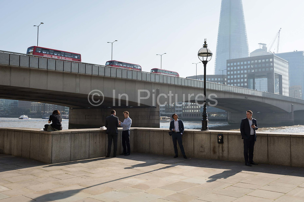 Londoners and office workers in the City of London - the capitals financial district - enjoy late summer temperatures on Fishmongers Hall Wharf overlooking the Shard skyscraper, London Bridge and the Thames river, on 10th October 2018, in London, England.