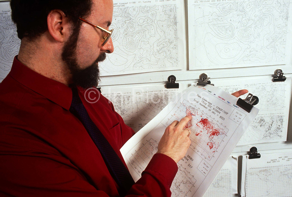 """An employee with 1990s weather chart technology at the European Centre for Medium-Range Weather Forecasts (ECMWF), Reading, UK. ECMWF is an international organisation supported by 31 States, its role is """"to provide monthly and seasonal-to-interannual forecasts; to deliver real-time analyses and forecasts of atmospheric composition; to carry out climate monitoring through regular re-analyses of the Earth-system and to contribute towards the optimization of the Global Observing System."""""""