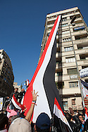 Protesters under a  gaint Egyptian flag lowered from an apartment in Tahrir Square.  A crowd gathers a week after Mubarak was forced to step down for a million man gathering to celebrate victory in Tahrir Square and answer a call to prayer in honer of those who died for the revolution.  Millions gathered in three different squares around Cairo a week after Mubarak's regime fell.