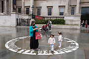 After seasonal Spring rainfall, young twins walk through an empty busker's circle, on the paved area in front of the National Gallery in Trafalgar Square on 24th May 2021, in London, England.