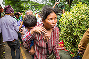16 JUNE 2014 - ARANYAPRATHET, THAILAND: A Cambodian woman carries her son after they got off a train at the end of the train line in Aranyaprathet, Thailand. They were among the thousands of Cambodians going back to Cambodia Monday. More than 150,000 Cambodian migrant workers and their families have left Thailand since June 12. The exodus started when rumors circulated in the Cambodian migrant community that the Thai junta was going to crack down on undocumented workers. About 40,000 Cambodians were expected to return to Cambodia today. The mass exodus has stressed resources on both sides of the Thai/Cambodian border. The Cambodian town of Poipet has been over run with returning migrants. On the Thai side, in Aranyaprathet, the bus and train station has been flooded with Cambodians taking all of their possessions back to Cambodia. PHOTO BY JACK KURTZ