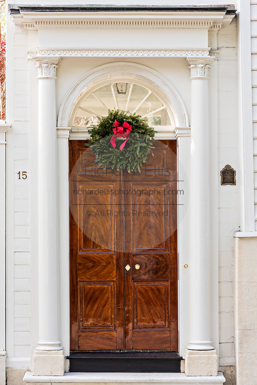 A wooden door on a historic home decorated with a Christmas wreath on King Street in Charleston, SC.