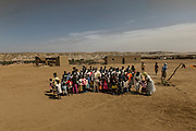 Tchikuteny with his sons ?s, at the village. In Angola?s Namibe desert, at Giraul, in the Namibe province, Tchikuteny, from the Mucubal tribe, is the leader of a big family, maybe the biggest family in the world.<br /> He is the chief leader, the manager and responsible for the entire village. <br /> In his village, Tchikuteny lives nowadays with most of his big family, his 33 wives, that were once 43, but 10 left the village, and most of their descendants.<br /> Tchikuteny maintains the registry of all the new-borns, totalizing 154 sons, and his grandsons, that are around 60. Nowadays, 4 new babies are on the way, and 3 great grand children were born recently.<br /> Huge harmony, love and respect transpire in the village atmosphere. The sense of a community is the pillar of their sustainability and sustenance and their autonomy depends prominently on cattle and agriculture that is made by the villagers. Nevertheless, Tchikuteny village is in close connection with their surrounding communities. Children attend Giraul School and there is proximity and relations with the extended family that lives in the surroundings.<br /> Being the spiritual leader of the community, Tchikuteny is also responsible for the weekly religious works that happens in the village church. <br /> This big family opened his doors to share with us their daily lives.