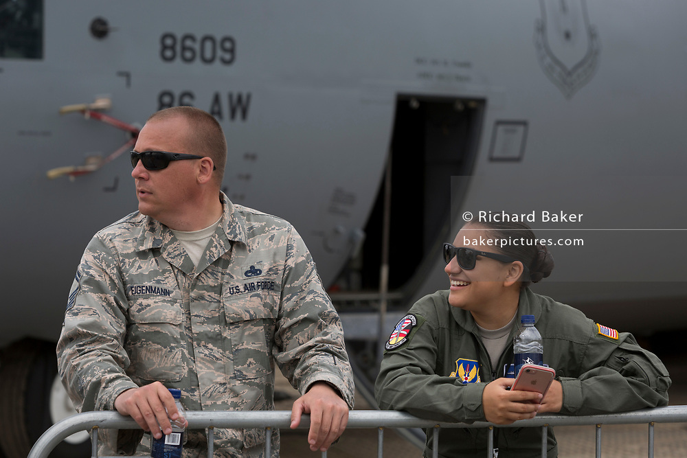 A serviceman and woman with the US Air Force stand in front of their C-130 aircraft at the Farnborough Airshow, on 18th July 2018, in Farnborough, England.