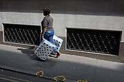 A women carries two large packs of toilet rolls into nearby offices, the capitals financial district, on 19th April, in the City of London, England.