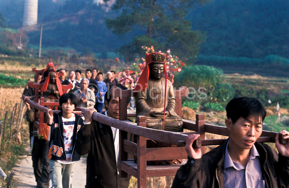 """Haka festival procession with Buddha weaving its way through village in a thunderous blaze of fireworks. <br /> The festival, which is called in Chinese """"Miao Hui"""" takes place only once every 8 years for the Que Ken Ba Village. Villagers go to Chao Tian Yan temple to carry the Guan Yin Buddha (God of Mercy) back to their village's temple. (Sept.19-22 is the festival time, chinese calender) keep for a year, to protect the villagers, bring them good luck, happiness and fortune. At the end of the year, Sept.19 following year, the village send back the Buddha to Chao Tian Yan temple, and another village will carry it to their village's temple. there are 8 villages in this festival, so by turn, every village get a chance every 8 years. Chao Tian Yan temple dates back 700 years ago. The special festival has started since then, was only stopped for around 20 years because of Culture revolution. It<br /> began again during late 1980s."""