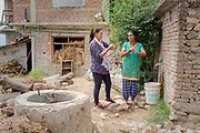 Local ENPHO staff member, Radhika Ghamire, teaching local mother of two, Srijana Phuyal, the technique for effective hand washing., Kakani, Nuwakot District, Nepal