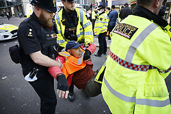 © Licensed to London News Pictures. 25/10/2021. London, UK. Police detain Insulate Britain activists as they block Bishopsgate in the City of London. The group have restarted their actions to block motorways and major roads causing disruption in the week before the COP26 climate meeting in Glasgow on 31/10/2021. Photo credit: Peter Macdiarmid/LNP