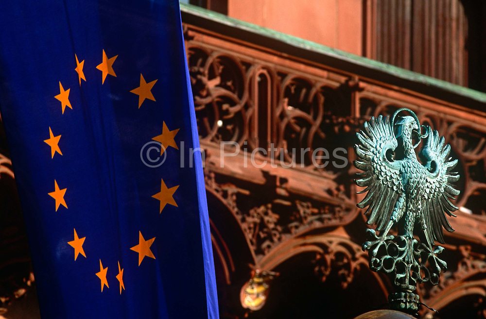 """The EU flag hangs limply alongside the old German world Prussian eagle near the balcony of Frankfurt's Rathaus or Town hall in historic Romerberg Square. The yellow stars formed into a circle of the European Union member states lie on a background of blue but the bronze green eagle harks back to a previous era of German politics and culture. The state of Prussia developed from the State of the Teutonic Order. The original flag of the Teutonic Knights had been a black cross on a white flag. Emperor Frederick II in 1229 granted them the right to use the black Eagle of the Holy Roman Empire.[citation needed] This """"Prussian Eagle"""" remained the coats of arms of the successive Prussian states until 1947."""