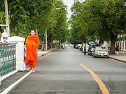 """21 JULY 2013 - BANGKOK, THAILAND:   A Buddhist monk walks along a street near Wat Benchamabophit on the first day of Vassa, the three-month annual retreat observed by Theravada monks and nuns. On the first day of Vassa (or Buddhist Lent) many Buddhists visit their temples to """"make merit."""" During Vassa, monks and nuns remain inside monasteries and temple grounds, devoting their time to intensive meditation and study. Laypeople support the monastic sangha by bringing food, candles and other offerings to temples. Laypeople also often observe Vassa by giving up something, such as smoking or eating meat. For this reason, westerners sometimes call Vassa the """"Buddhist Lent.""""      PHOTO BY JACK KURTZ"""