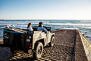 Couple parked up on the slipway in their landrover watching the surf and waves in low sunlight at St Ouen's Bay, Jersey, CI